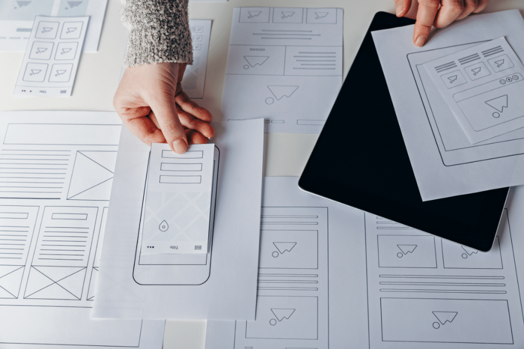 Picture of a hand laying down a piece of paper with different web elements above an image of a phone. This is to illustrate building a user experience on mobile. All around this image lay images of different web layouts.