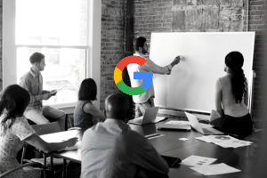 Image of a meeting taking place with someone writing on a whiteboard. In the middle is Google's colored icon